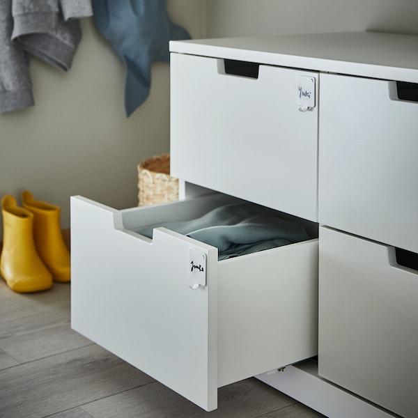 Cómoda de caixóns cun caixón aberto. Os caixóns teñen no frontal ganchos PLUTT con nomes escritos para facilitar a organización.