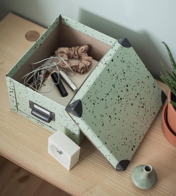 Comodino con una scatola aperta contenente cuffie, elastici per i capelli e altri oggetti - IKEA