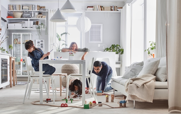Compact-living home where a family plays with a LILLABO train set in a room with bed, sofa, table, kitchenette, and storage.