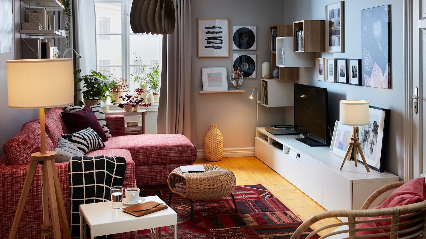 Compacte woonkamer met aan één zijde een slaapbank met chaise longue; dressoir, opbergruimte, tv, stereo en kunst aan de andere kant.