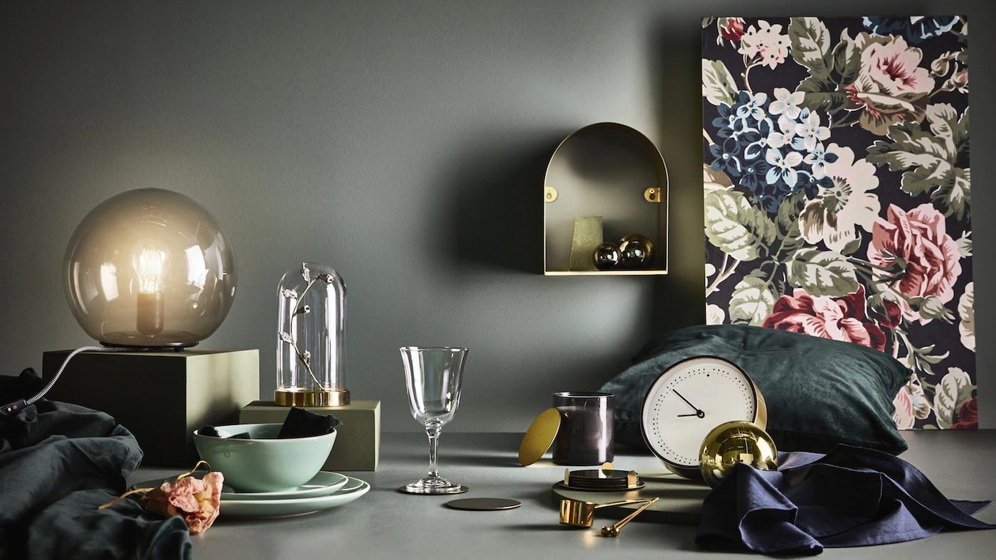 Composición de elementos decorativos sobre un fondo oscuro formado por una copa, un reloj, una lámpara de mesa y un fanal o campana de vidriol, entre otros.