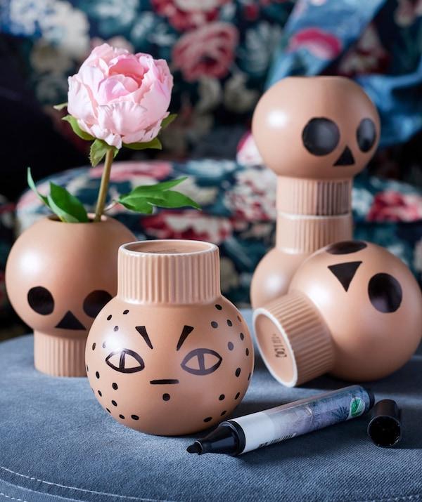 Con un rotulador de pizarra, se han pintado caras terroríficas sobre pequeños jarrones.