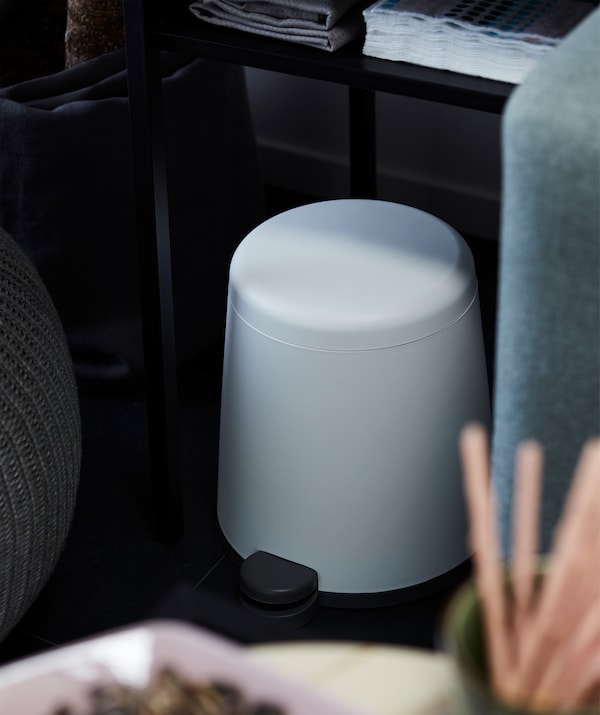 Cone-shaped with rounded corners, a SNÄPP pedal bin stands placed half under a table between sofa and pouffe in living room.