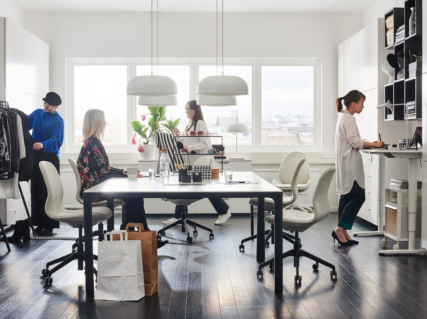 Contemporary white office setting including BEKANT white sit-stand desks and black shelving organisation units.