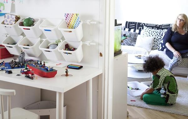 Contenedores cuelgan de una barra montada en la pared para crear un almacenamiento de juguetes en un dormitorio para niños. Una madre y su hijo sentados en un segundo plano.