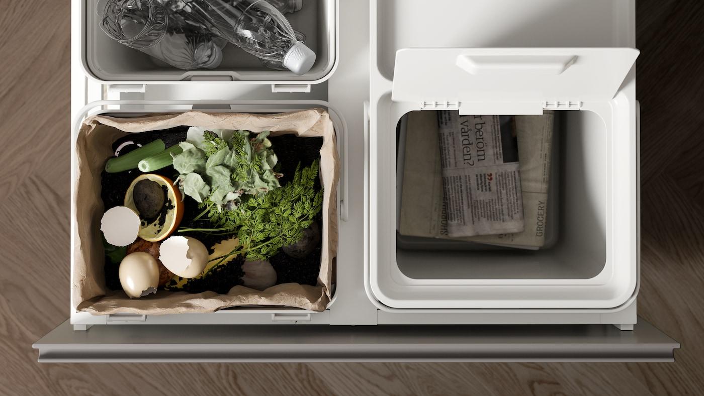 Contenedores de reciclaje blancos HÅLLBAR. Se ve la división de basura orgánica como comida, con papel como el papel de diario y plásticos como botellas.