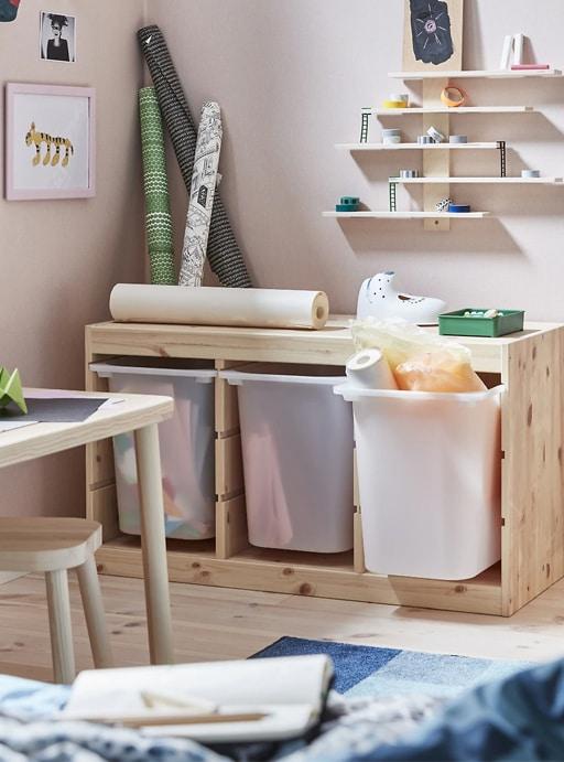 Contenedores profundos en un mueble de madera clara, con material de arte y estantes arriba.