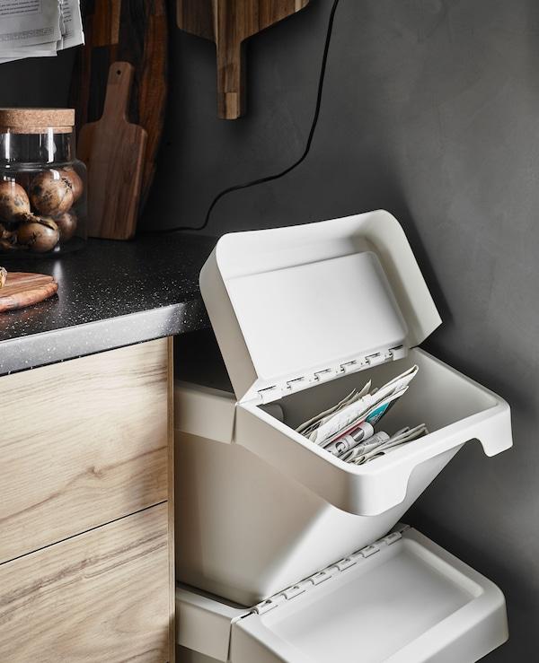 Conteneurs à déchets avec couvercle empilés dans un espace vide sous le plan de travail d'une cuisine, au bout d'une rangée d'armoires basses aux portes à motif frêne.