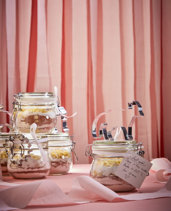 Cookie dough ingredients are layered in glass jars, with a handwritten note and cookie cutter attached.