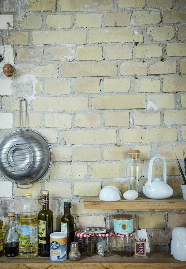 Cooking ingredients on open shelving against a brick wall.