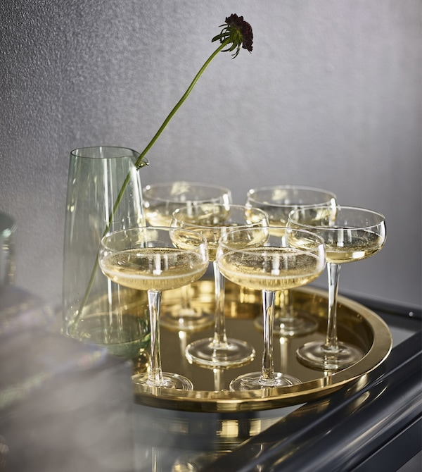 Copas de champán sobre una bandeja GLATTIS de acero metalizado de color bronce.