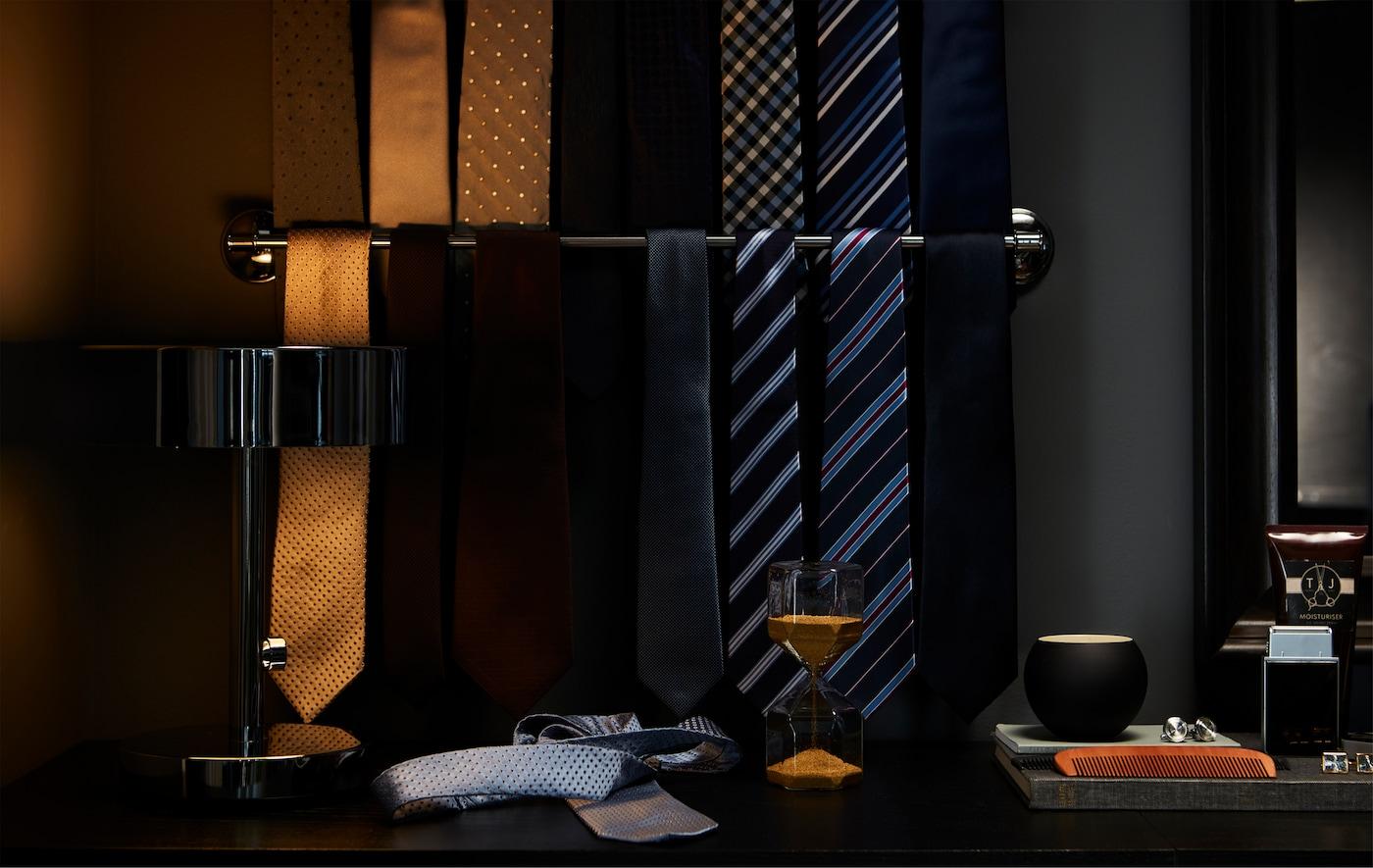 Corbatas en marrón dorado, azul, negro, gris y rayas colgadas en un toallero cromado IKEA para facilitar la visión.