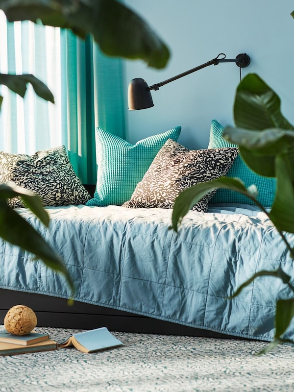 Corner bed in a blue bedroom and blue quilt and pillows in different textures