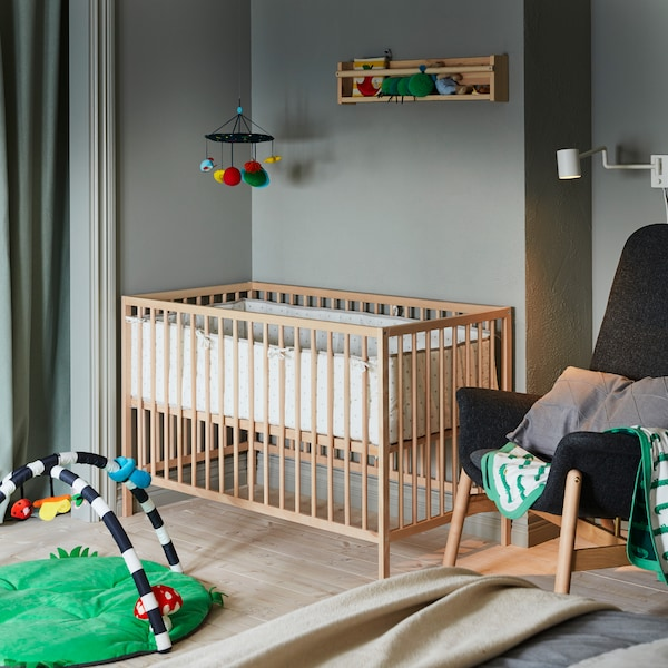 Corner of a bedroom with a wooden baby's cot. An armchair on one side, a baby gym on another, a mobile hanging above.