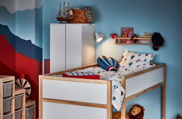 Corner of a kid's room with a reversible bed in loft position, a ledge shelf with book and toys, and a lit bed light.
