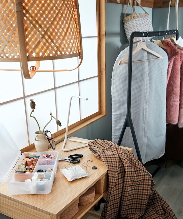Corner of a room arranged for mending clothes: sewing kit and coat on a side table next to a rack of clothes awaiting their turn.
