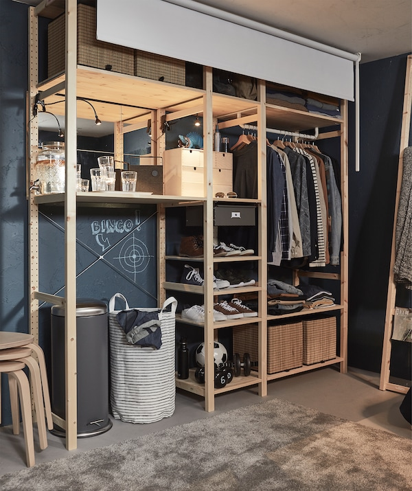 Corner of a room with a large shelving unit filled with clothing; a fitted black-out roller can be rolled down in front.