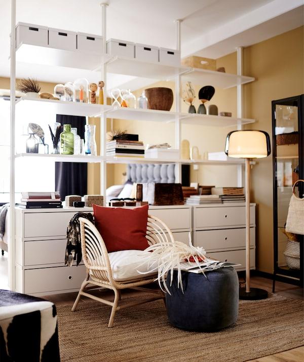 Corp de depozitare modular, alb, folosit ca despărțitor al camerei într-o cameră de zi cu plan deschis.