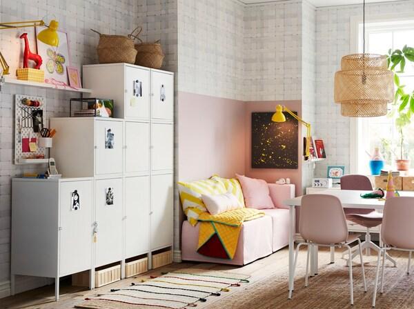Corpuri albe HÄLLAN care ocupă puțin spațiu, folosite pentru depozitare, așezate în fața unui perete, într-o cameră de zi cu roz, alb și galben.