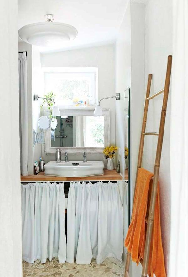 Cortina de tela blanca que esconde artículos de baño detrás del lavabo en un cuarto de baño pequeño y blanco.
