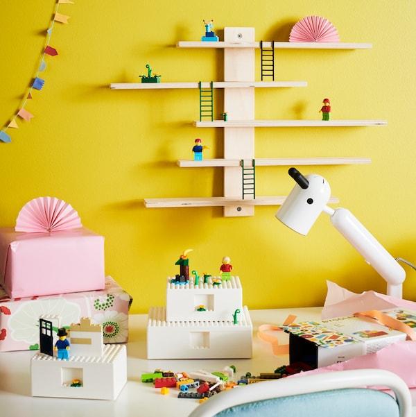 Costruzione BYGGLEK LEGO® accanto alla sua scatola parzialmente rivestita con carta rosa. Vicino ci sono dei regali incartati davanti a una parete gialla.