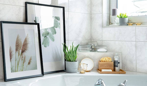Cosy bathtub decorated with IKEA picture frames and other accessories.