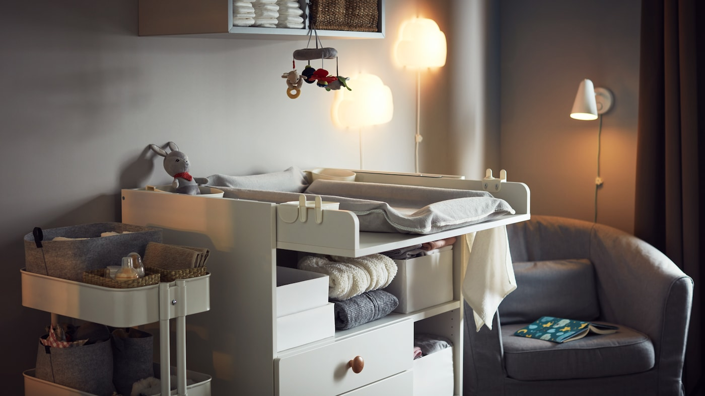 Cosy warm room with changing table, storage trolley with baby accessories, armchair, night wall lamps and wall storage.