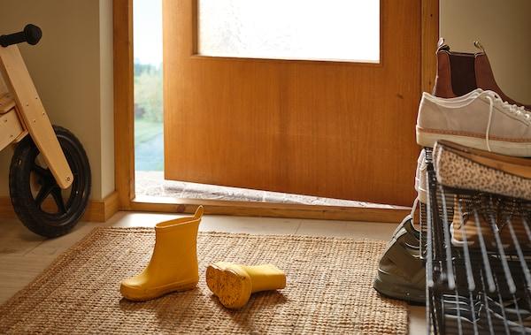 Couloir avec une paire de bottes de pluie pour enfants sur le tapis, étagère à chaussures remplie sur le côté, vélo d'enfant en bois contre le mur.