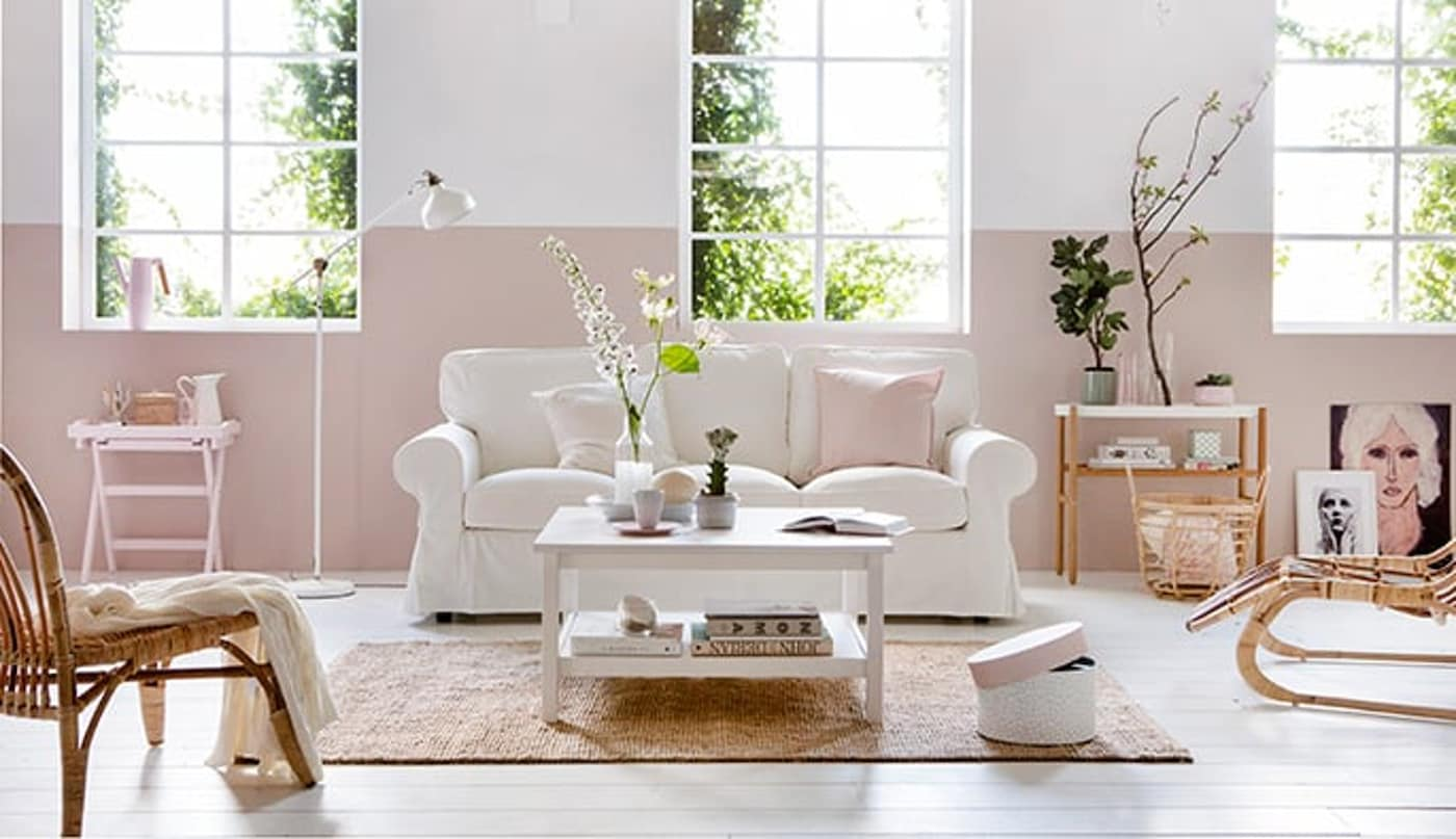 Country-style interiors with white sofa, rattan chairs, home accessories and light pink panel on the wall