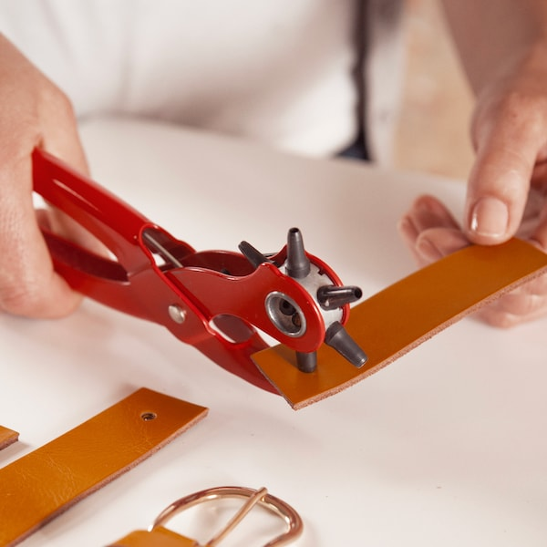 Coupez une vieille ceinture en cuir en morceaux de 12 cm et faites deux trous dans celle-ci avec une pince.