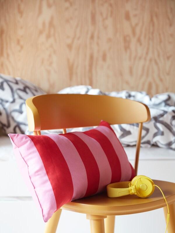 Coussin rayé rose clair et rouge installé sur une chaise pour enfant jaune vif, et écouteurs jaunes assortis.