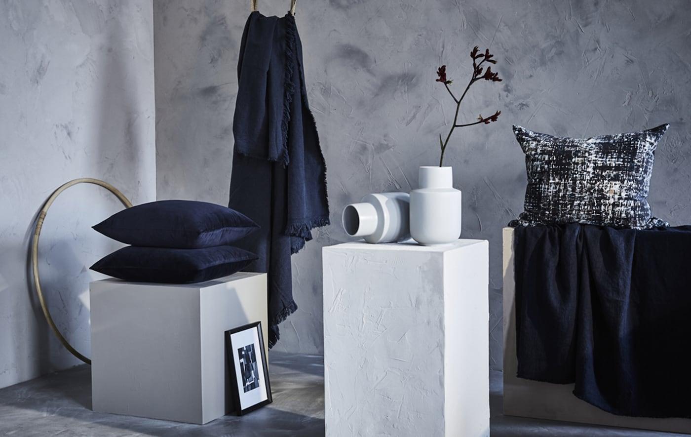 Coussins et plaids bleus exposés dans une pièce en gris et blanc.