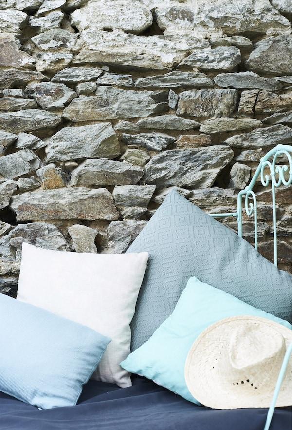 Coxíns en distintos tons de azul en fronte dunha parede de ladrillo.