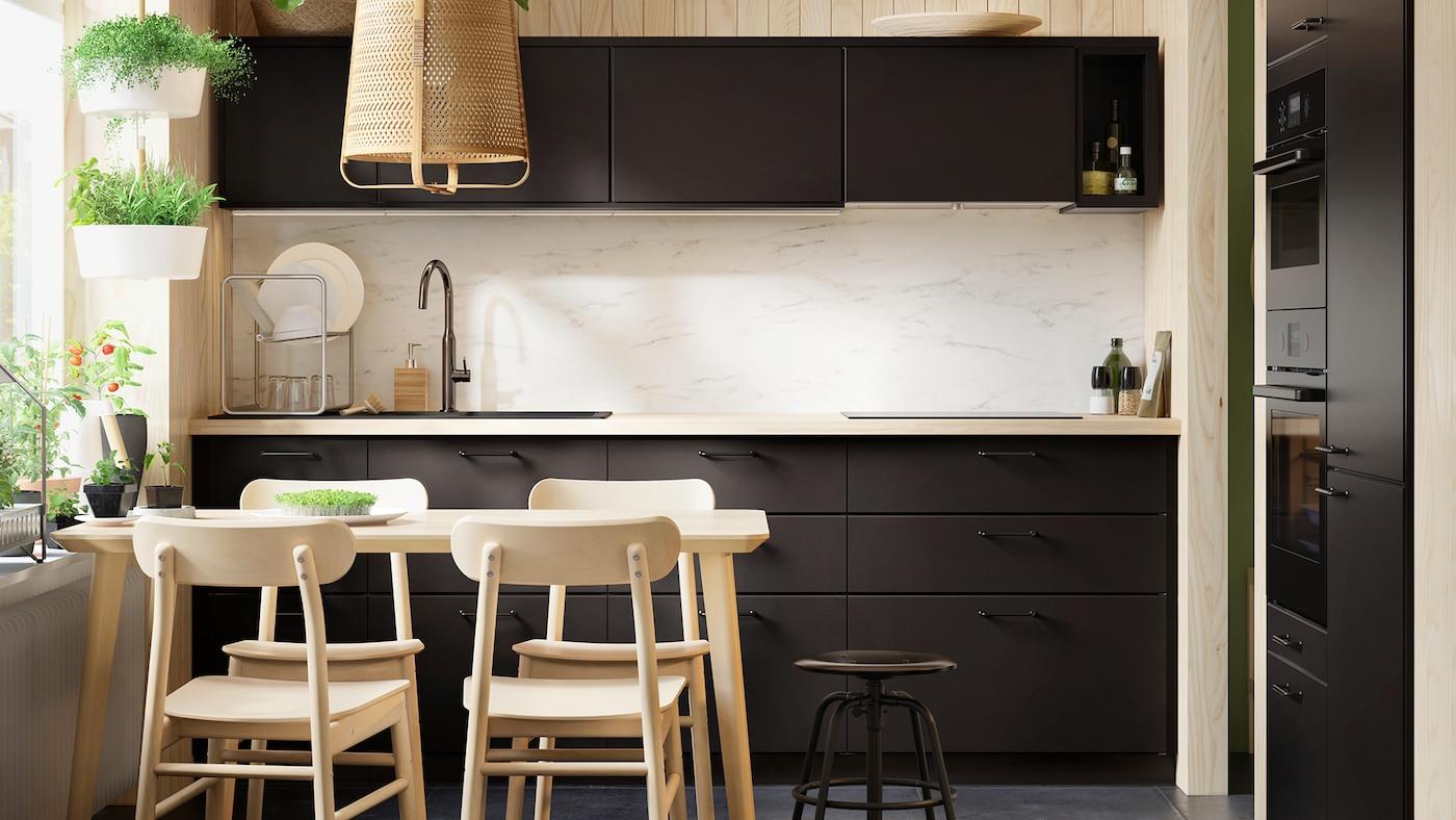 Cozinha com frentes escuras e uma mesa de refeição com cadeiras em madeira clara.