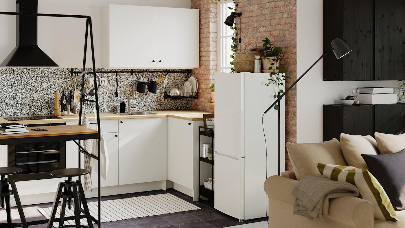 Cozinha de canto em antracite/cinzento, um carrinho em preto, um tapete às riscas e recipientes em preto com ervas aromáticas.