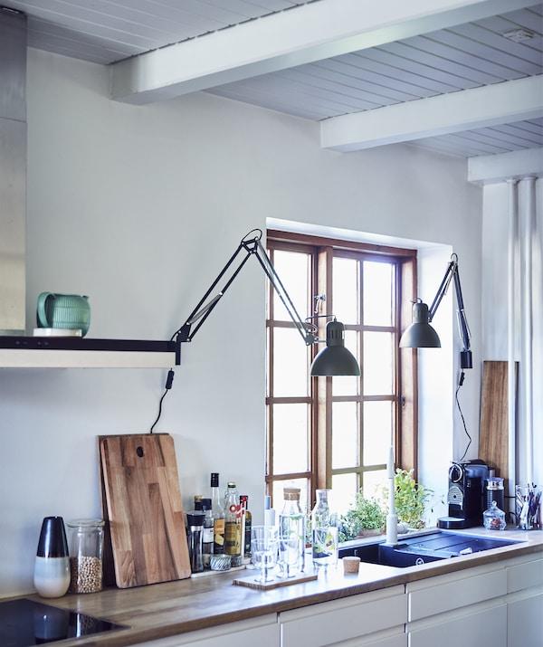 Cozinha em branco com dois candeeiros de secretária instalados na parede