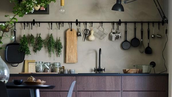 Cozinha escura e acolhedora com armários e gavetas em preto, paredes de madeira preta e prateleiras e bancadas em branco.