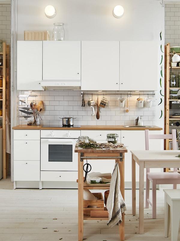 Cozinha KNOXHULT com frentes em cinzento claro, paredes com painéis em verde e forno. Ao fundo, um espaço de refeição.