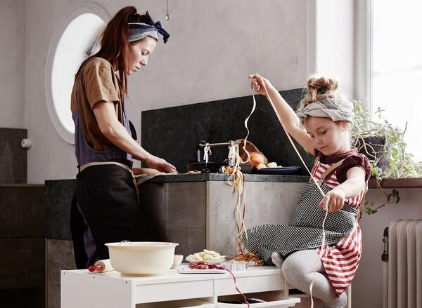 Cozinha onde uma mãe lava a loiça enquanto a filha arranja uma grinalda.