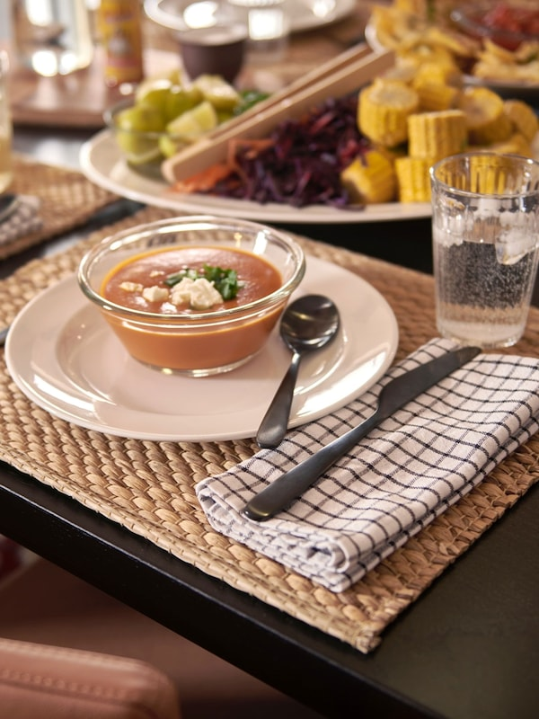 Cozy dining room table setting with bowl of soup sitting on UNDERLAG natural place mat