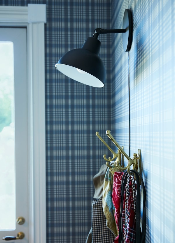 Create a hook hanging storage station with IKEA KAMPIG brass swivel hooks and SKURUP mounted black wall lamp. There are three hooks in each to hold more.