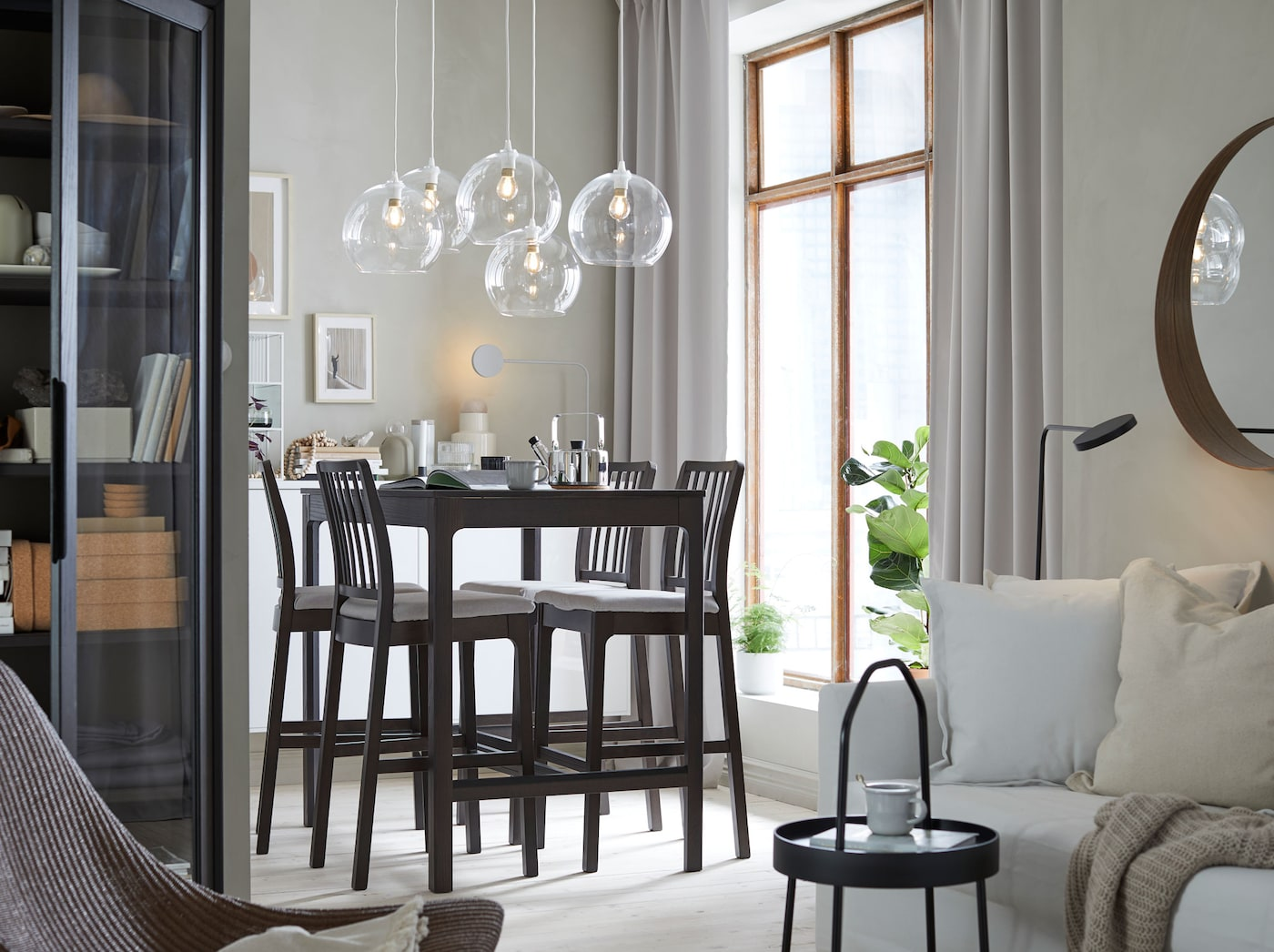 Create a simple yet classic dining space and living room space using EKEDALEN dark grey four-seater bar table and high bar stools, along with soft white HOLMSUND sofa bed and JAKOBSBYN clear glass pendant lampshades.
