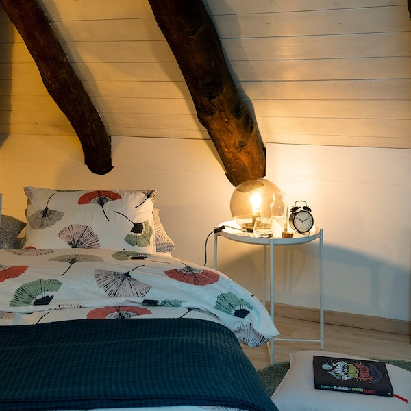 Créer une atmosphère chaleureuse sous la pente du toit avec une table GLADOM et une lampe IKEA.