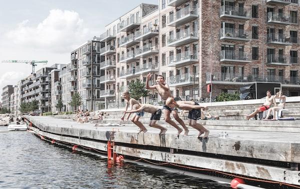 Crianças a mergulhar para um rio junto a blocos de apartamentos.