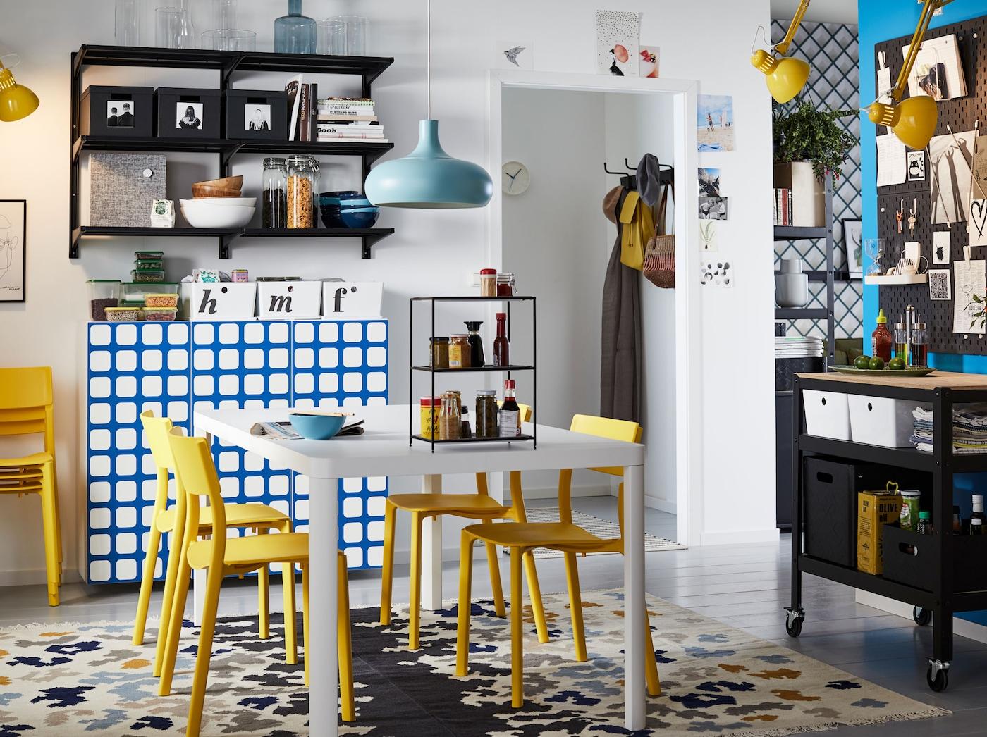 Crie o seu espaço de refeição partilhado com a mesa de refeição TINGBY, leve e em branco, as cadeiras JANINGE, em amarelo, e a despensa aberta com as prateleiras ALGOT para uma limpeza fácil e acesso à loiça.