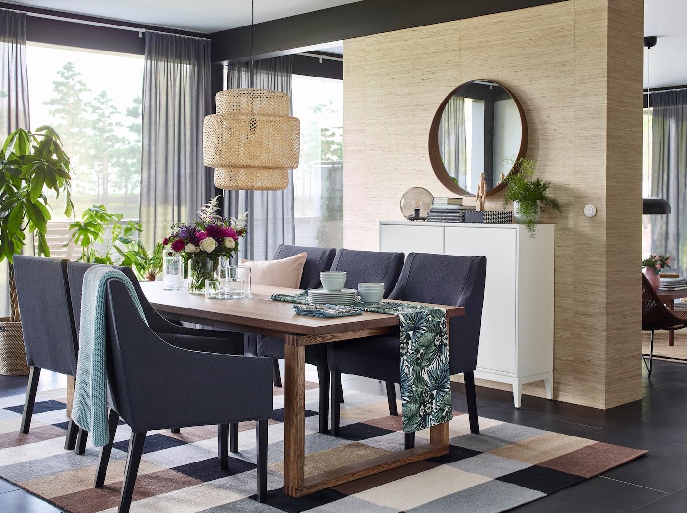 Crie um espaço de refeição com um tema natural, colocando o tecido TORGET em tons verdes sobre a mesa e o candeeiro de teto SINNERLIG feito em bambu, um material natural.