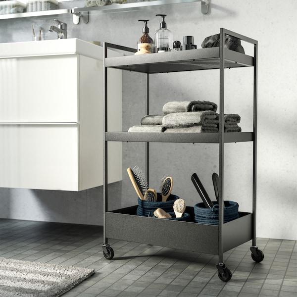 Crna kolica u bijelo-sivoj kupaonici. Na njima se nalaze sapun, ručnici i četke, a postavljena su pokraj umivaonika.