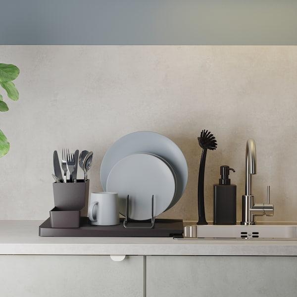 Crni oceđivač suđa s posuđem za serviranje u sivim i plavim nijansama i priborom stoji pored ugradne sudopere od nerđajućeg čelika.