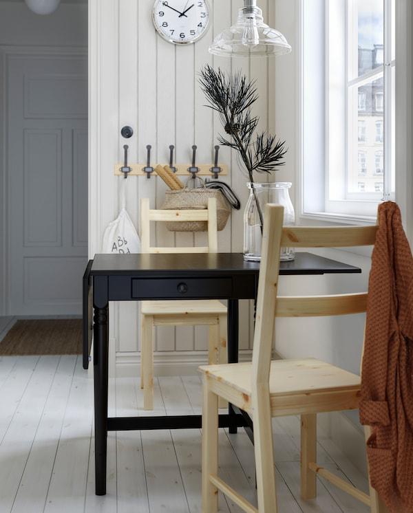 Crni preklopni sto s fiokom, dve stolice od borovine, drveni stalak s kukama, zidni sat i staklena visilica.
