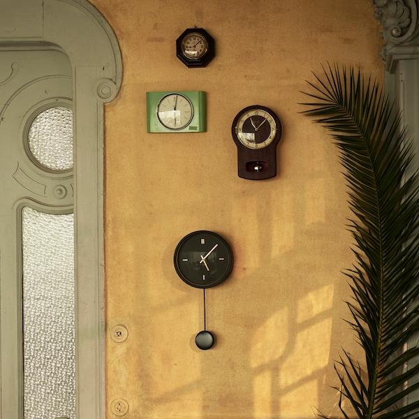 Crni STURSK zidni sat sa zlatnim detaljima i klatnom koje visi s njega. Postavljen je na zid s drugim starim zidnim satovima.